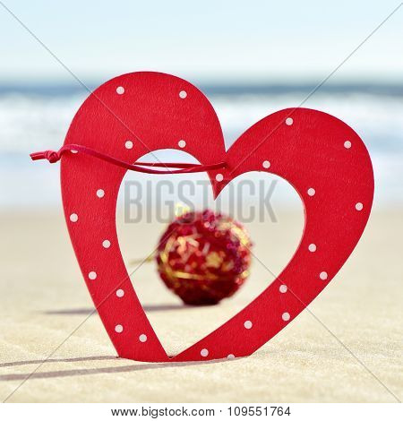 closeup of a red heart-shaped ornament and a red christmas ball on the sand of a beach