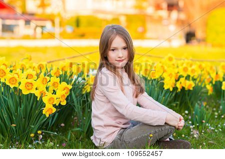 Adorable little girl playing with flowers in the park at sunset