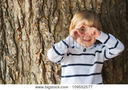Little 4 year old blond caucasian boy in front of an old and massive tree