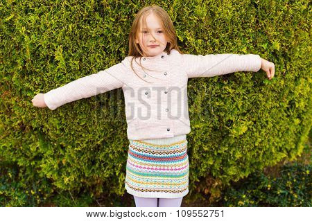 Outdoor portrait of a cute little girl wearing jacket, playing with a big bush