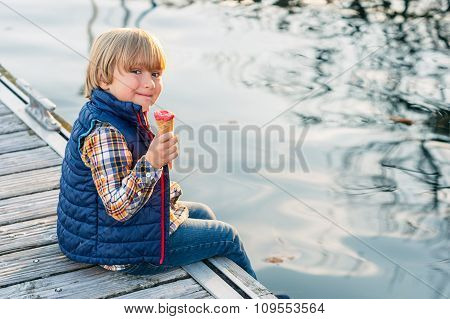 Cute little boy eating ice cream by the lake