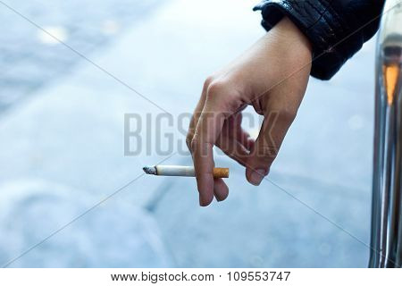 Womans Hand With Cigarette In The Street.
