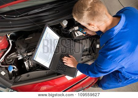 Mechanic Using Laptop To Repair Car