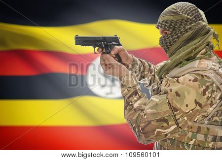 Male In Muslim Keffiyeh With Gun In Hand And National Flag On Background - Uganda