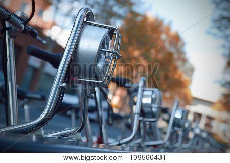 Row of bikes parked on sidewalk.