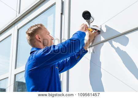 Technician Fixing Camera On Wall