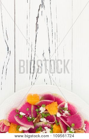 Colorful and healthy watermelon radish orange and goat cheese carpaccio salad. Top view free text co