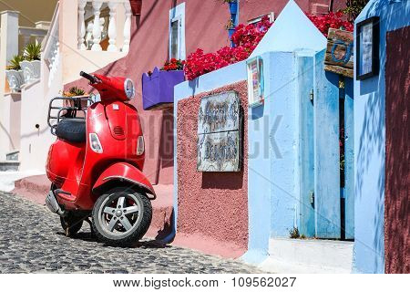ed motor scooter as a part of decoration at color street of Thira town