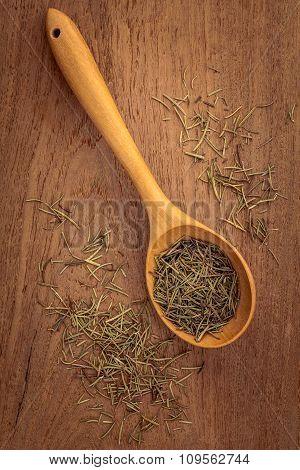 Dried Rosemary Leaves In Wooden Spoon On Teak Wood  Background .