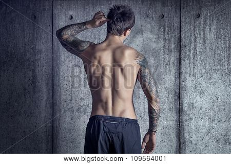 sportfit muscular tattoed guy from back in loft space