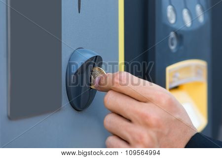 Person's Hand Inserting Coin At Parking Meter