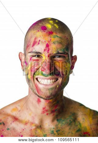 Smiling young man with skin all painted with Holi colors