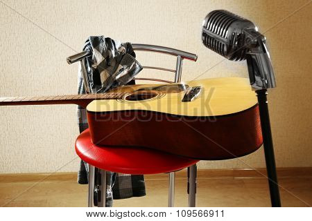 Guitar on red stool and microphone in the studio, close up