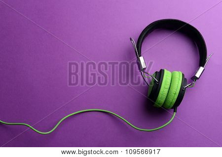 A pair of green-black headphones, on purple background
