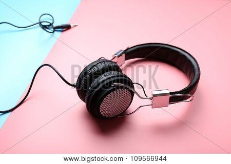 Black headphones on pink-blue background
