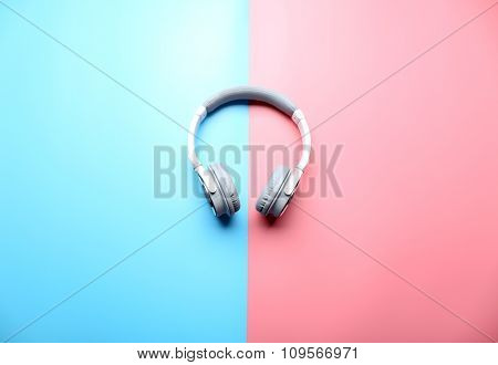 Wireless white and grey headphones on pink-blue background