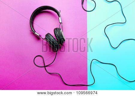 Black headphones on purple-blue background
