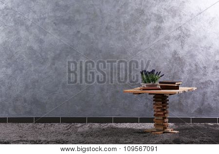 Small wooden table, books and lavender on grey wall background