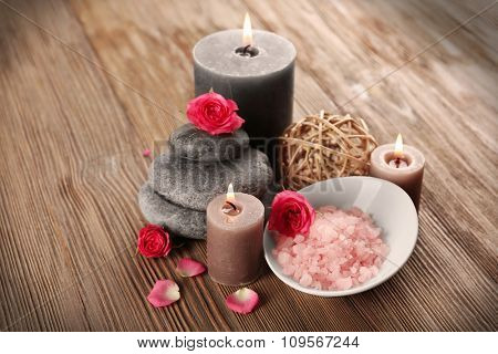 Relax set which include aroma candles, flowers, petals and pebbles on wooden background