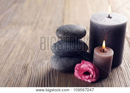 Alight wax grey candles with roses and pebbles on wooden background - relax concept