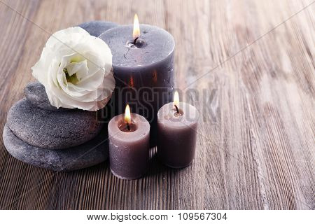 Aroma candle with pebbles and flower  on wooden background