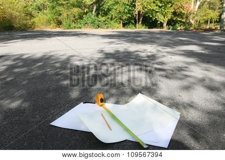Papers and tape-measure with pencil on the street