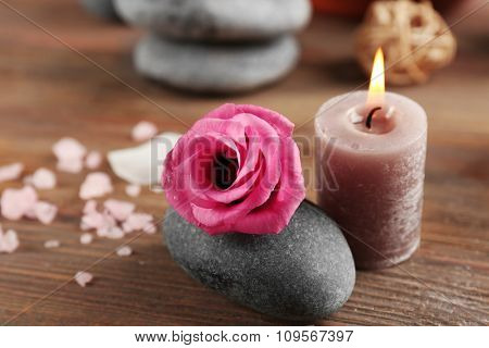 Beautiful composition of aroma candle with pebbles and flower  on wooden background
