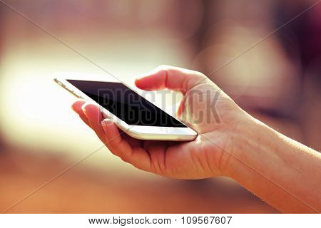 Hand holding smart phone on bright background