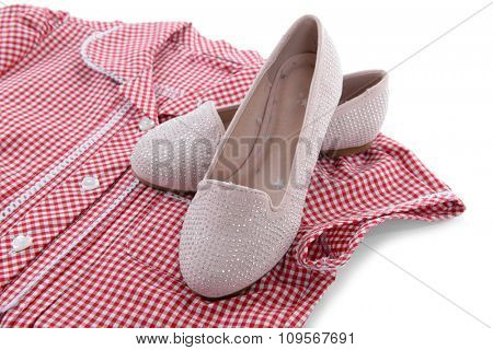 Shiny pink shoes and red plaid shirt on white background