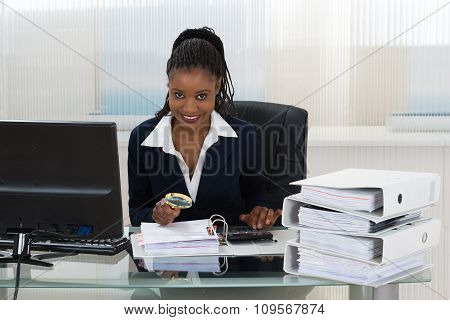 Businesswoman Holding Magnifying Glass Over Invoice