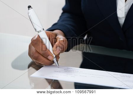 Person's Hand Signing Cheque