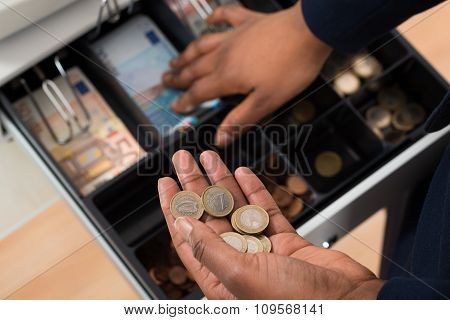 Person's Hand With Euro Note Over Container