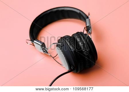Black headphones on pink background