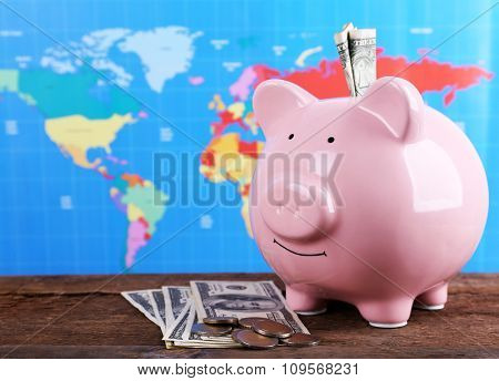 Piggy money box, banknotes and coins on wooden table