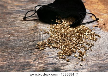 A pouch with scattered gold nugget grains, on wooden background
