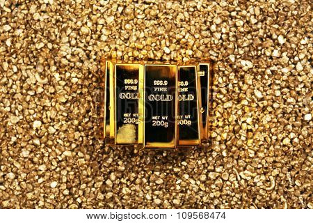 Gold bars on nugget grains background, close-up, top view