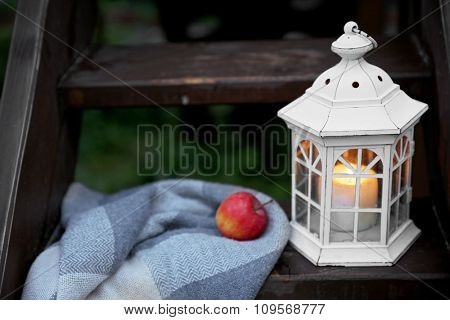 Lantern with candle on wooden stairs, on mountains background