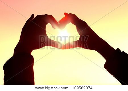 Hands in shape of love heart on sunlight background
