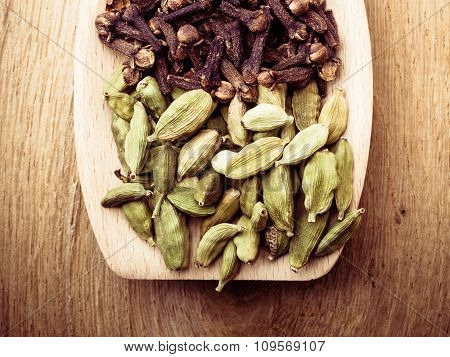Cardamom Pods And Cloves On Wooden Spoon