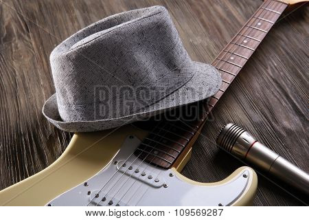 Electric guitar with hat on wooden background