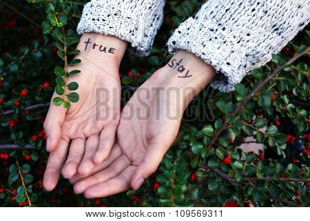 Hands of young woman with tattooed words on it, on green bush background, close-up