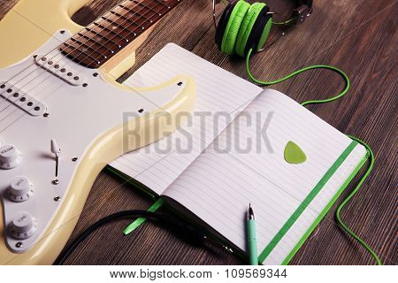 Electric guitar with green headphones and note book on wooden background