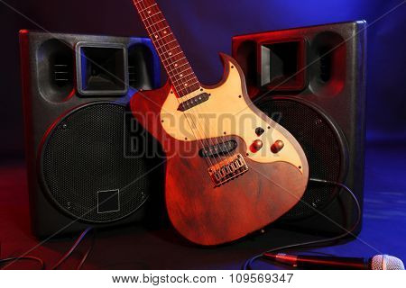 Big black loudspeakers with electric guitar and microphone on colourful background, close up