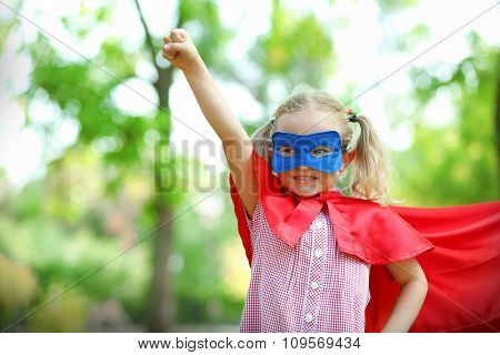 Superhero little girl plays at the park
