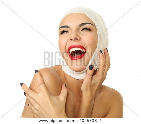 Young emotional woman with a gauze bandage on her head and chest, isolated on white