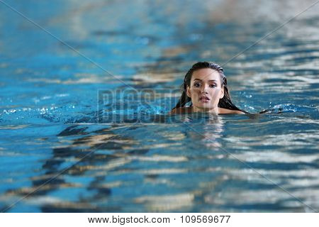 Beautiful young woman swimming in pool