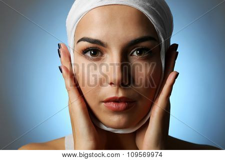 Young beautiful woman with a gauze bandage on her head, on grey-blue background, close-up