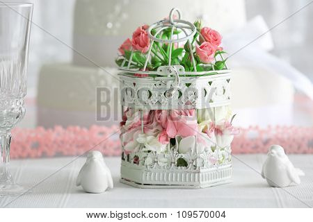 Flowers in cage and birds on wedding cake background