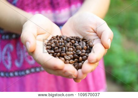 Woman holds in hands roasted coffee beans, heart shaped