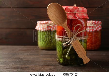 Jar of canned cucumbers and tomatoes on wooden background